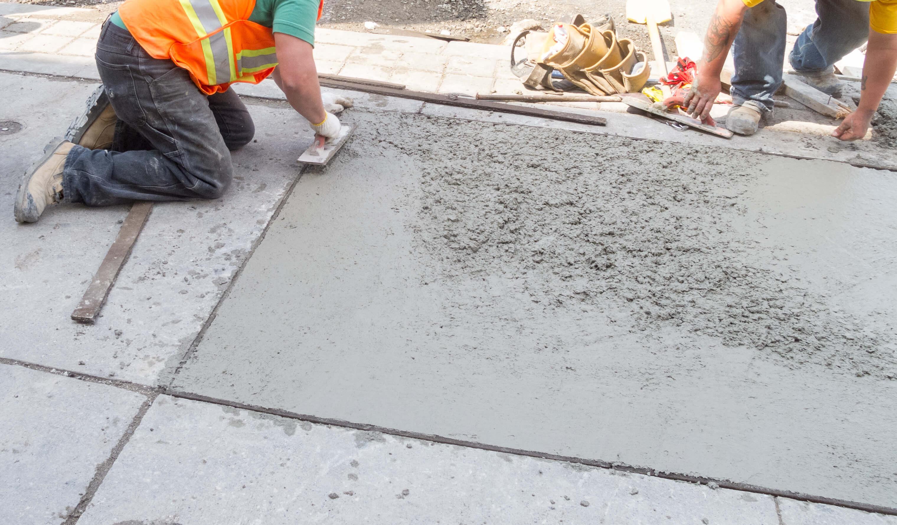 Bauarbeiter beim Geißen von Betonplatten für Gehwege