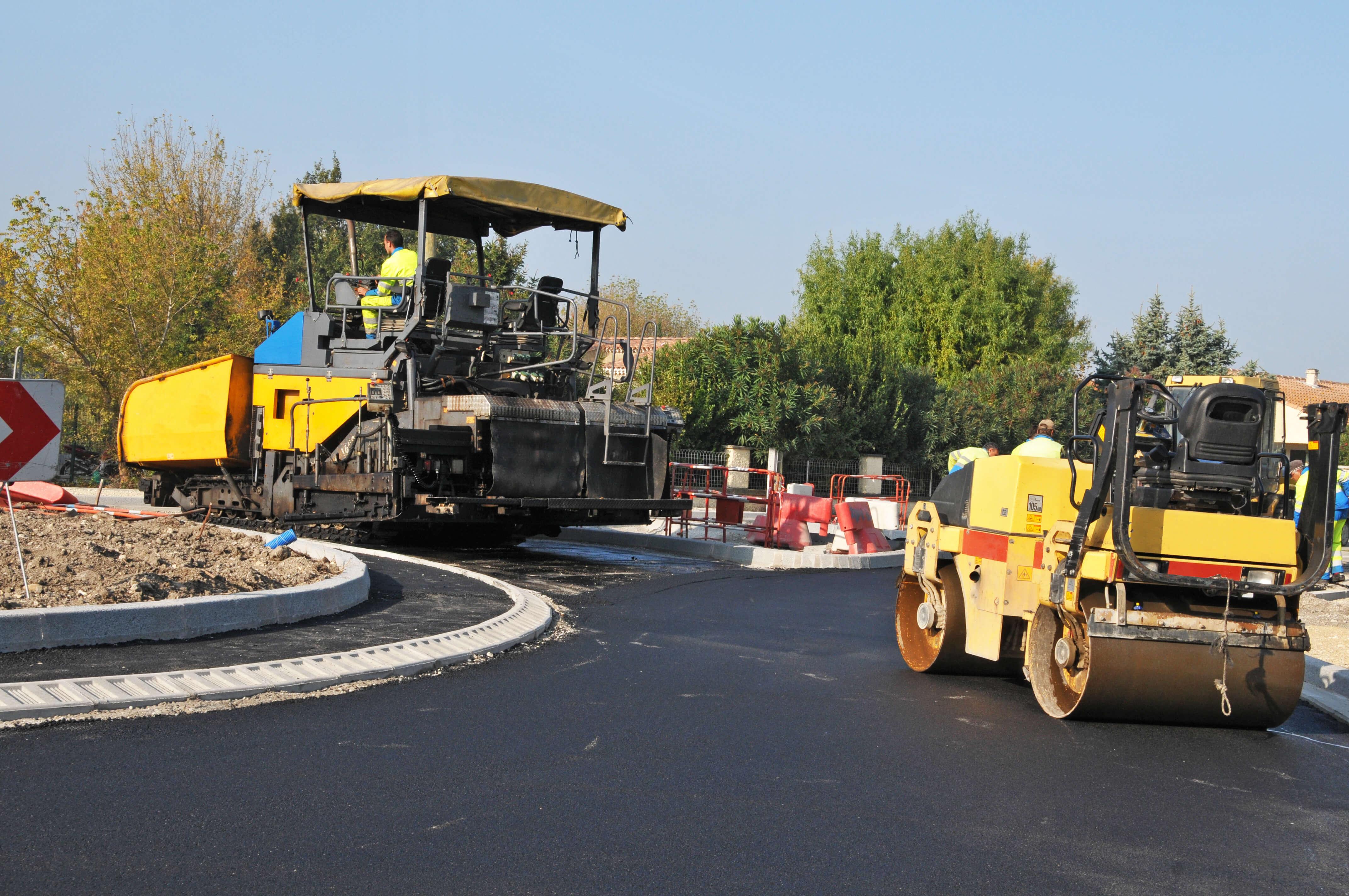 Baumaschinen beim neuen Asphaltieren von einem Kreisverkehr